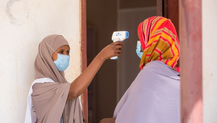 Amram Ismail, a 24 year old pregnant mother of 5, has her temperature checked as part of the Covid 19 routine protocols, prior to receiving antenatal care a