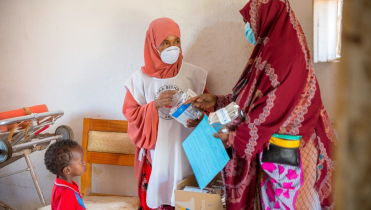Nura Abdi Abdilahi, a SRCS volunteer and store keeper at the Allaybaday Clinic, dishing out food supplements